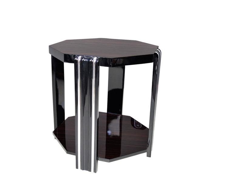 Art Deco style side table with carved feet and a Macassar veneer. With an octagonal tabletop with elegant chrome bars.   Refined with our signature black piano lacquer  made by hand with high quality materials in our manufactory in Senden,