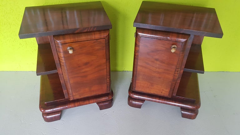 Beautiful pair of 1930s walnut nightstands from Sweden. Feature a small door with a brass handle each and a shelves for books. They are in a good original condition with just slight since of wear and convince with their beautiful walnut grain and
