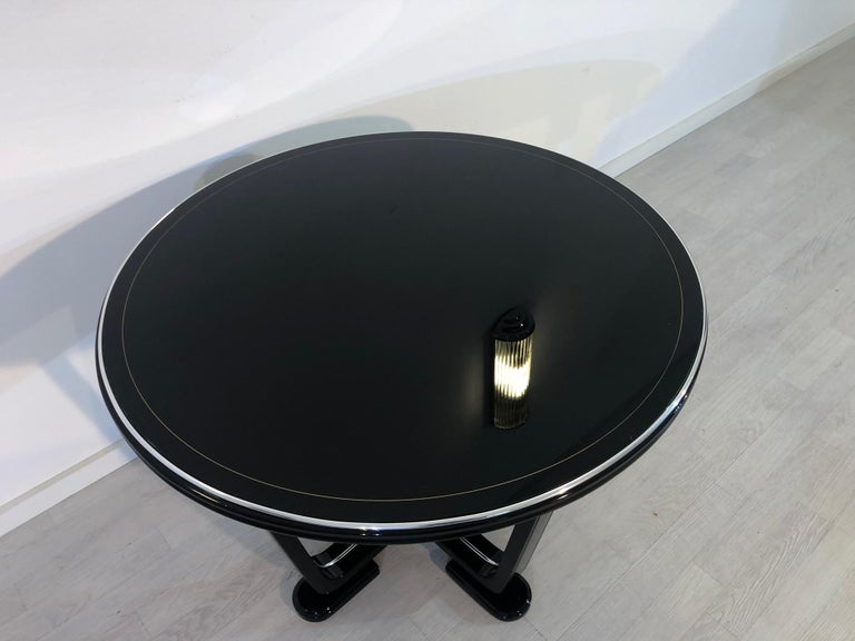 Elegant Art Deco end table or couch table from the 1920s with a diameter of 80cm. Convinces with its simple but luxurious design with filigree legs and high end piano lacquer. Refined with chrome bars and hand polished surfaces. In stunning, perfect