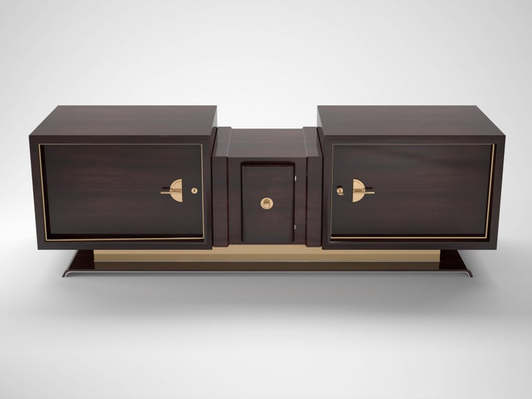 Luxurious Art Deco design sideboard or buffet made of dark walnut wood and elegant brass applications. The designs offers a three part body with large walnut doors and brass handles as well as a curved middle door. The foot convinces with big brass
