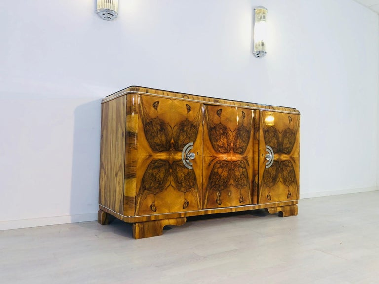 Stunning, original Art Deco sideboard from the 1920s.This masterpiece convinces with its unique burl veneer, a wonderful grain, and a vivid brown color. Made of French walnut wood and restored in our manufactory in Senden, Germany, the sideboard or