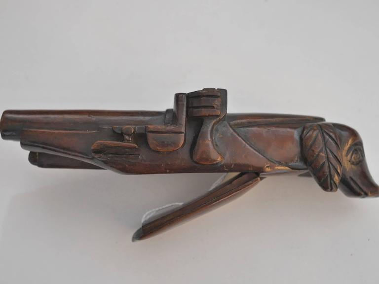 Mahogany wood carved snuffbox featuring a retriever on one side and a gun barrel on the other.  The tobacco was placed on the little box underneath.  This object belonged to the