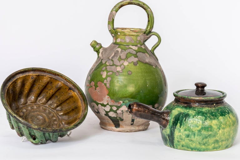 An assortment of French crockery as vases, vessels, plates, cooking mold, and creamers. Handmade and vintage, circa 1880.
