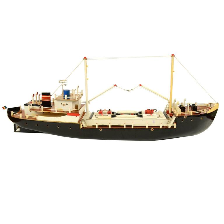 Scale model of a 1,000-ton boat depicting a small freighter used for the coastal cabotage. French flag, two derricks for loading and unloading cargo, central winch on the bow and smokestack on the stern. Made in 1950s. The model is made of wood,