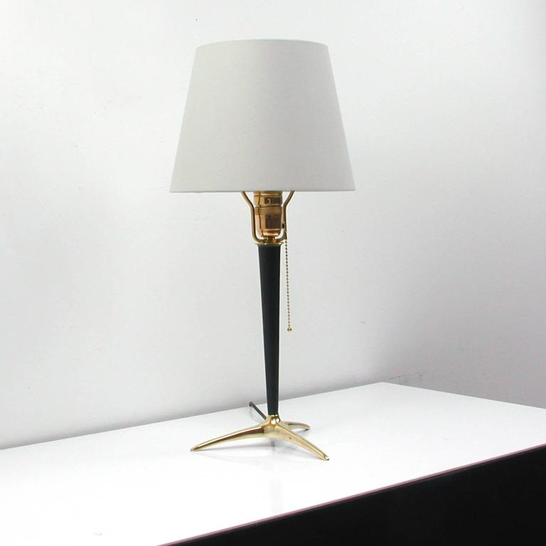 Tripod brass and black lacquered metal table lamp, made in Austria in the 1950s in the manner of J.T. Kalmar. The lamp shade is cream colored and new.