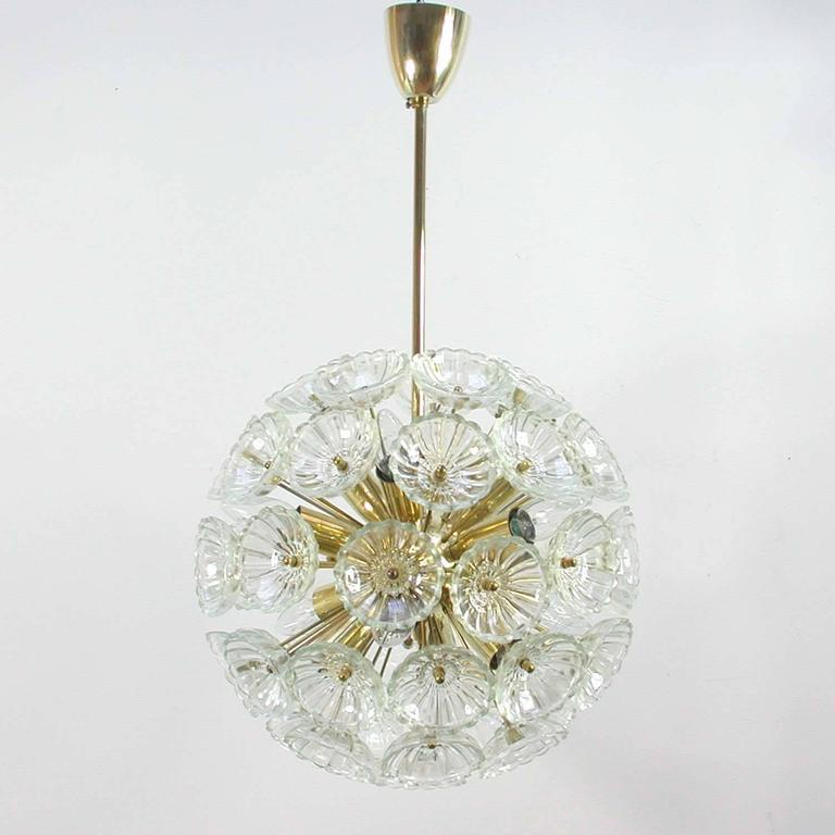 Awesome glass and brass dandelion chandelier, made in Germany in the 1960s. The chandelier has got twelve lights and 52 glass blossoms.
