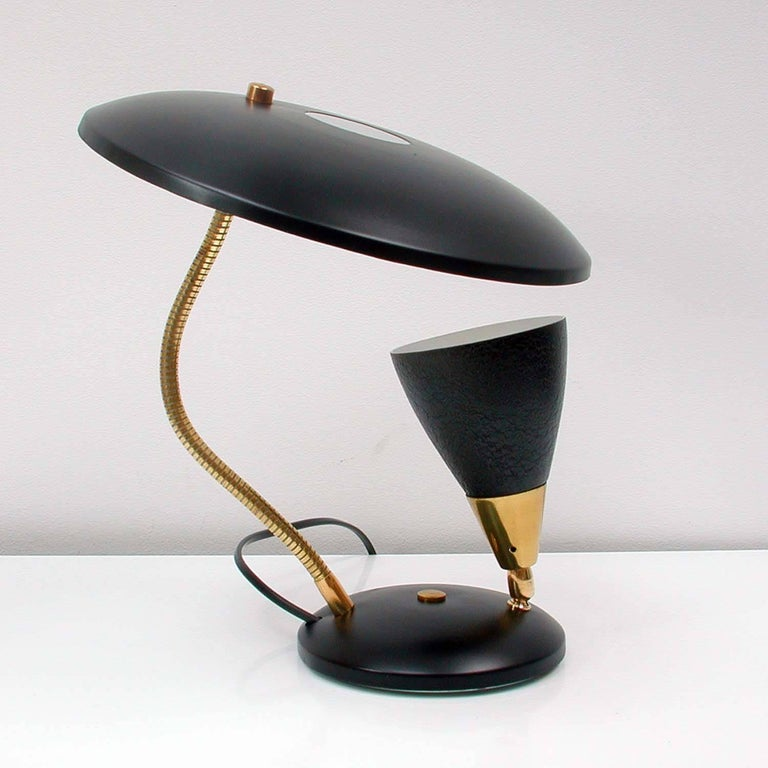 This Midcentury table light was designed and manufacrured in France in the 1950s.  It has got a black reflecting lampshade, a gooseneck lamp arm and an adjustable black and brass bulb holder. The lamp is in excellent vintage condition and has been