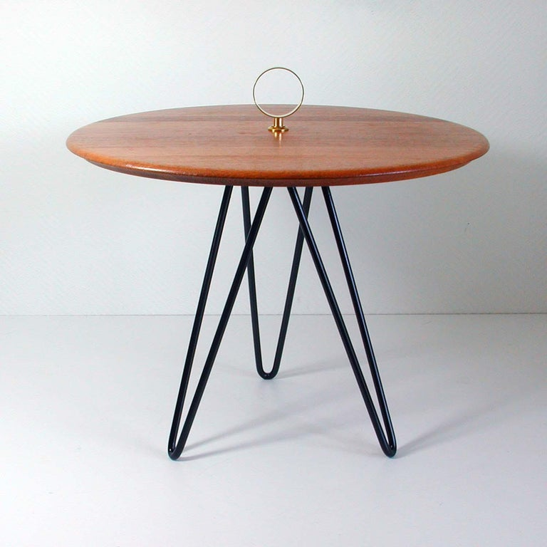 This round vintage tripod side table was made in Denmark in the 1950s to 1960s by Digsmed. It has a black lacquered cast iron string style base, a teak table top and brass details.