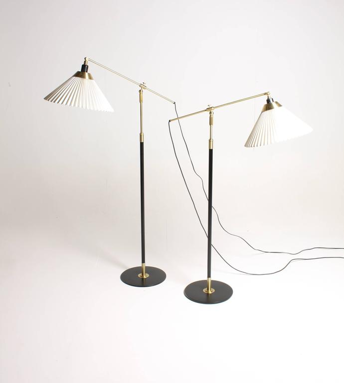 Pair of adjustable floor lamps in black painted metal and brass designed by Le Klint studio. Made in Denmark. Very nice original condition.