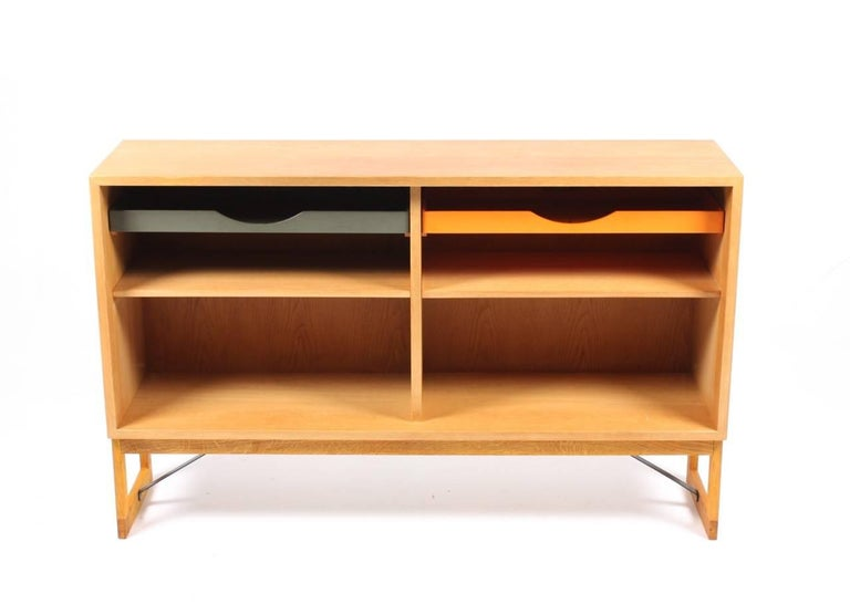 Low bookcase in oak with adjustable shelves and colored drawers. Designed by Danish architect Børge Mogensen for Karl Andersson cabinetmakers. Made in Sweden in the 1960s. Great original condition.