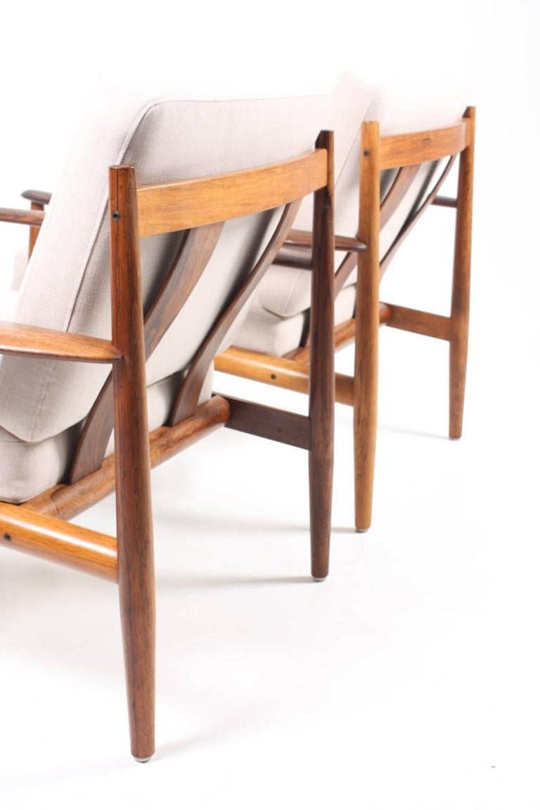 Pair of lounge chairs in solid rosewood, upholstered with new fabric. Designed by Grete Jalk for France, and son cabinetmakers. The chairs are made in Denmark, in the 1960s, and stands in great condition.