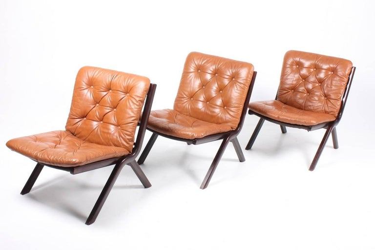 Set of three great looking lounge chairs in plywood and patinated leather designed and made in Denmark. Great original condition.  The lounge chairs are cleaned and waxed. Comes from a non-smoker home. Very nice original condition.
