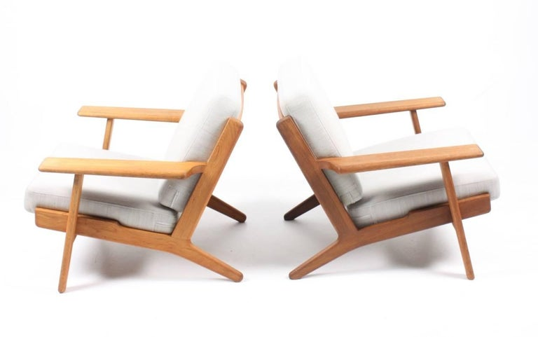 Pair of GE290 lounge chairs with frame in solid patinated oak, the cushions are reupholstered in light gray fabric by Gabriel. Designed by Hans J. Wegner for GETAMA Denmark. The chairs stands in great condition.