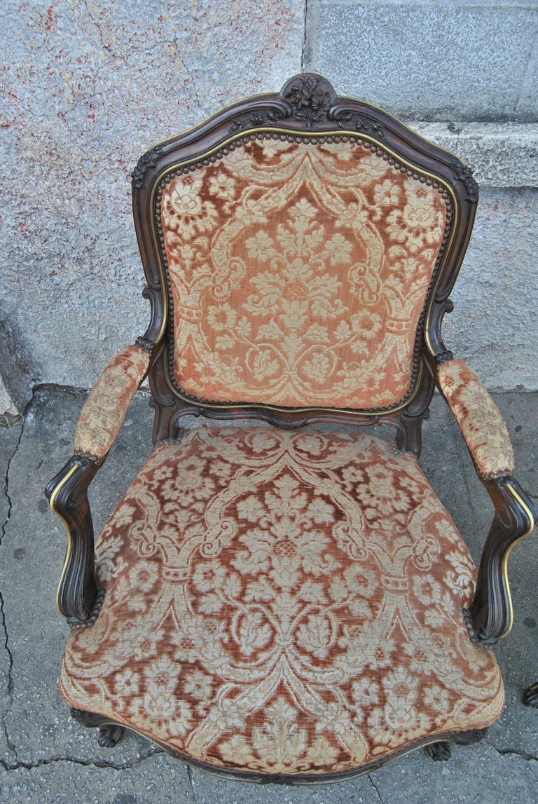 This is a pair of armchairs made in France, circa 1880. The chairs are made of solid rosewood. Each chair has beautiful hand carving of the finest quality. The chairs have a highly shaped back. The arms, the side of the chair frame and the