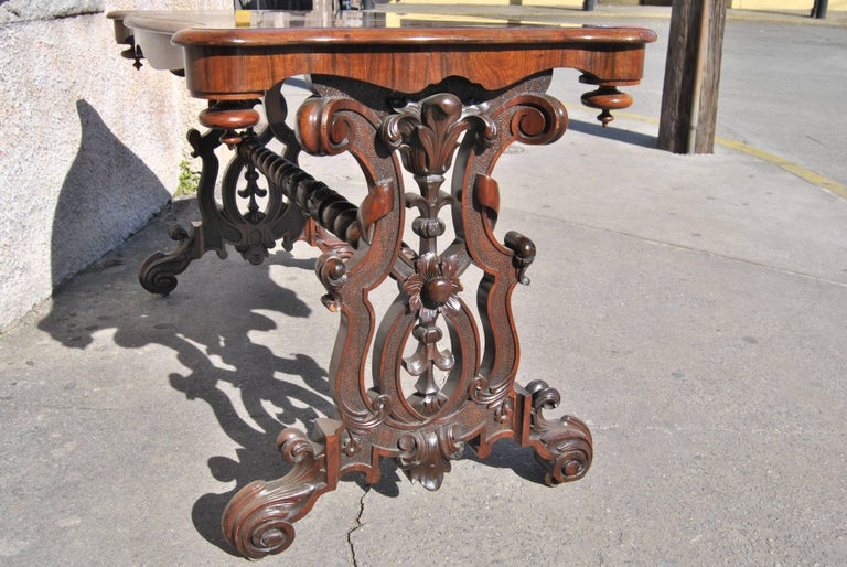 This is a rosewood table made in England, circa 1860. The table has a beautifully shaped top with a nicely molded edge. The top has a remarkable, highly figured Rosewood that is of the best quality. The pedestals on either end are highly carved and