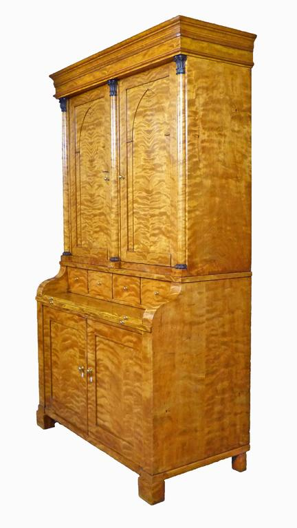 Elegant Biedermeier Secretaire Bureau Bookcase of finely figured satin birch. The upper section with two individual cupboards with interior adjustable shelves and one interior drawer each. On the exterior, the doors feature a lancet shaped design