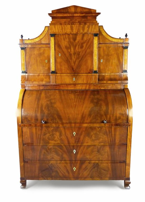 Fine and iconic figured mahogany Biedermeier cylinder bureau/secretaire with architectural top consisting of a central door flanked by two further doors all with applied birds eye maple columns with ebony capitals and drawers below, two of them