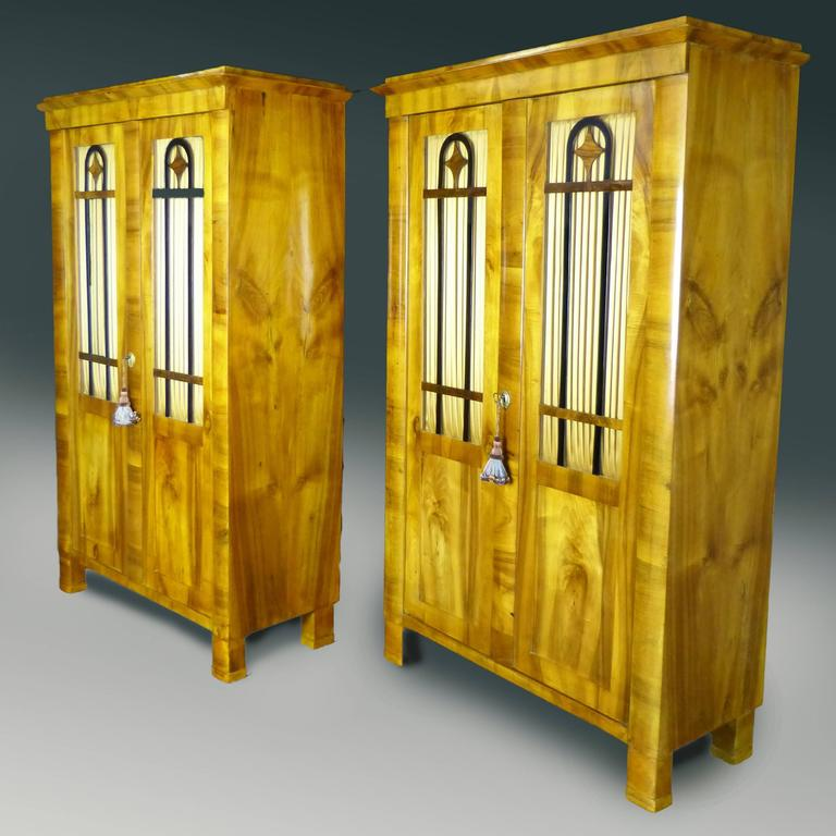 Outstanding and rare pair of period Biedermeier display cabinets / Bookcases of finely figured north European blond walnut exterior. Each display cabinet features three slightly curved frontal columns, two of them terminating below in block feet of