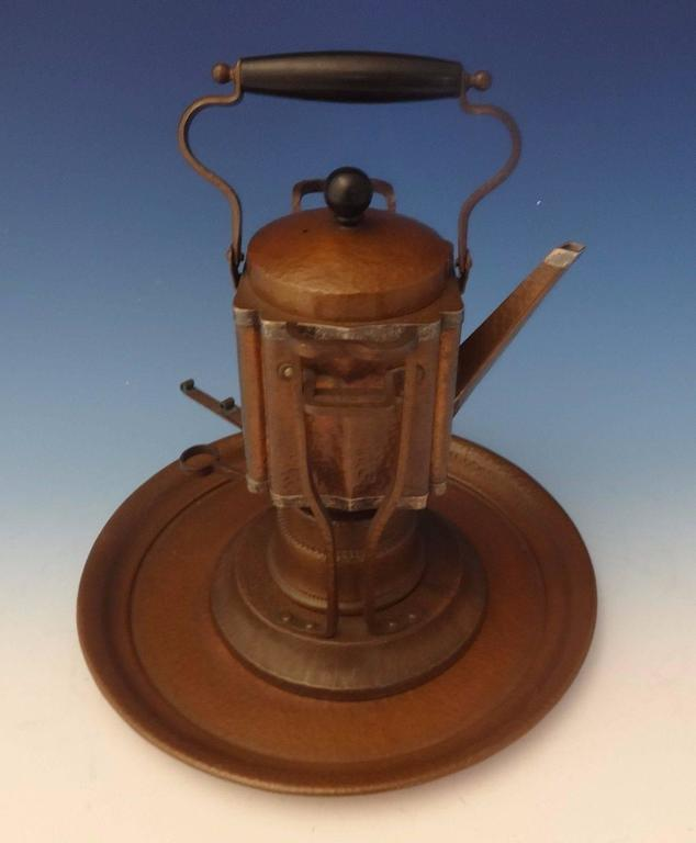 Joseph Heinrichs: Arts & Crafts kettle on stand and tray was handmade by Joseph Heinrichs. The piece is made of copper and with applied sterling silver, it's hand-hammered, and it dates from about 1905. The measurements for the piece are 13