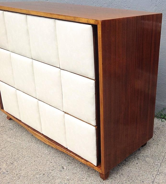 This padded front chest designed by Gilbert Rohde was introduced into the Herman Miller catalog in the fall of 1940. Simple sleek lines and rich mahogany and cream colored leatherette make this chest as relevant today as it was 70yrs ago. Tastefully