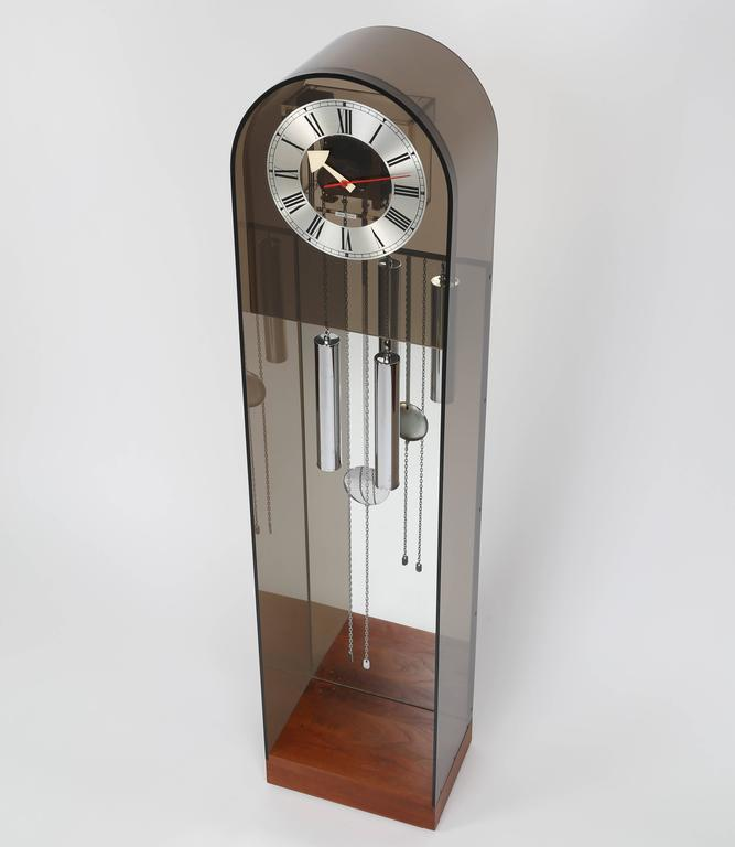 Howard Miller tall case clock in smoked Lucite with a walnut base, mirrored back, and chrome weights and pendulum. Mechanical movement is driven by traditional weights on chains. Howard Miller, Zealand, MI, USA, circa 1970s. Manufacturer label.