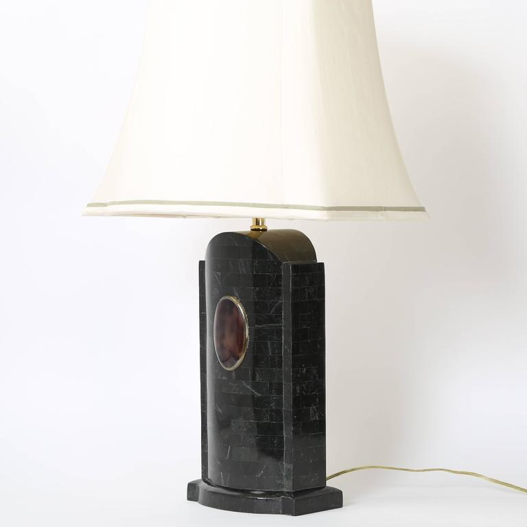 Pair of vintage Maitland Smith lamps clad in dark-green marble tiles. The front of each lamp base features an oval brown stone insert trimmed in brass. Well-made and substantial. Original circular stone finials and decorative silk shades included in