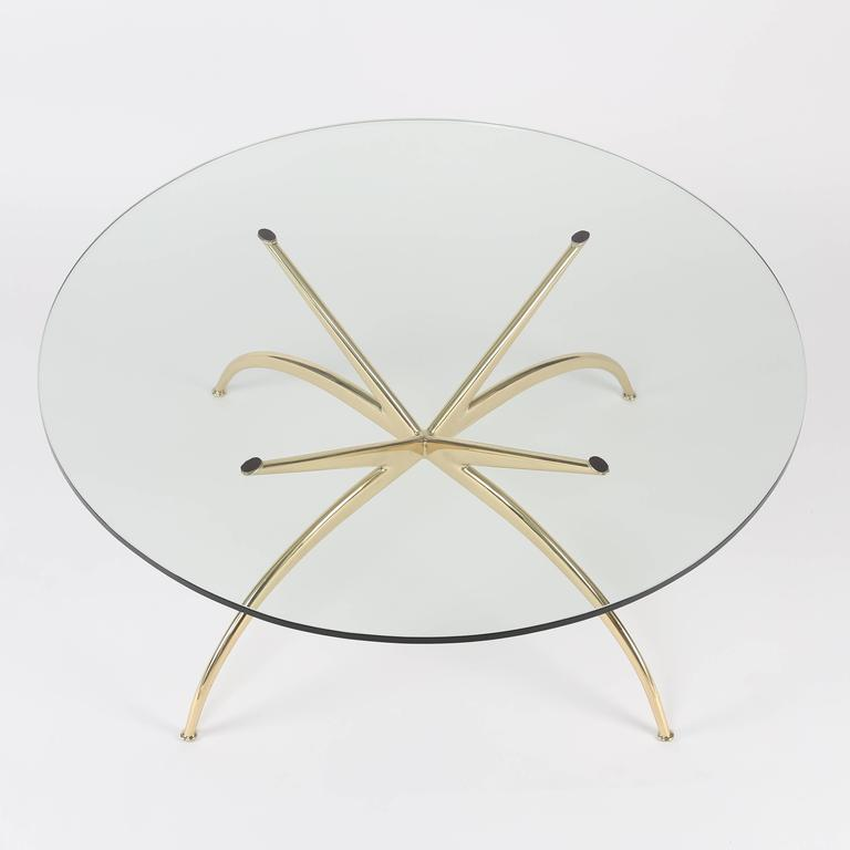 This 1950s Italian solid-brass coffee table features four gracefully arched and tapered legs connected to four straight tapered arms that support a round glass top. Overall 36