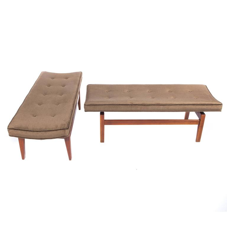 Pair of sturdy and stylish benches featuring four legs supporting a cantilevered, gently curved, button-tufted seat, circa 1960s. The walnut retains its original warm brown finish and the seats are newly reupholstered in medium-chocolate-brown