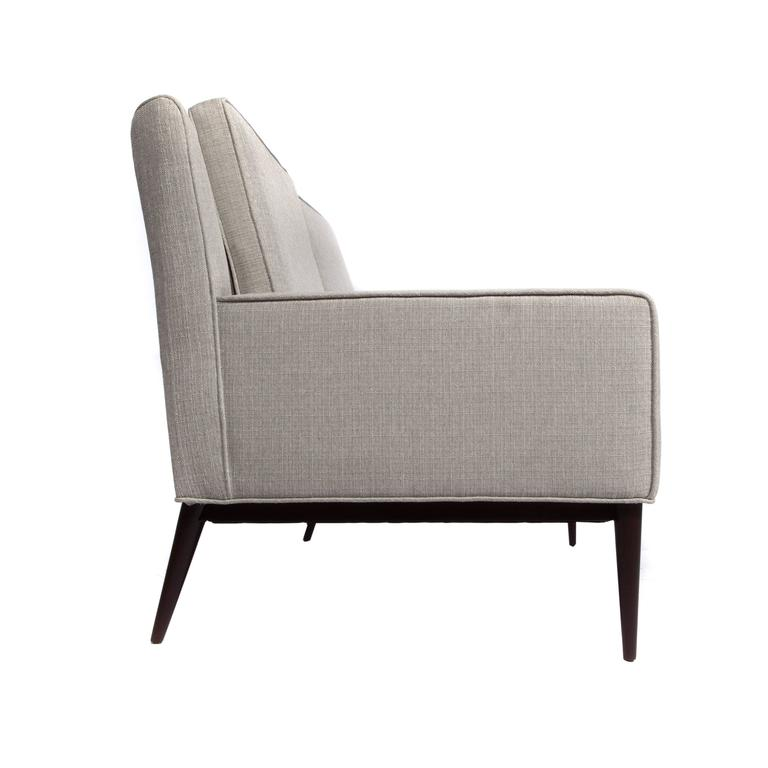 Chic, curved-back 1950s Paul McCobb loveseat floating on tapered and angled walnut legs. Newly restored and reupholstered in a light silver-gray woven fabric. Fabric swatch available.   See this item in our Brooklyn showroom, 61 Greenpoint Ave.,