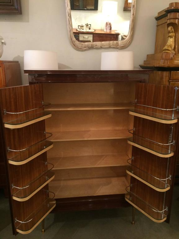 A fine Jules Leleu designed modernist two-door bar cabinet. Mahogany marquetry details on the doors, resting on patinated gilt bronze legs. Interior door shelves  crafted in polished nickel with mirrored bottoms.  Complete professional restoration