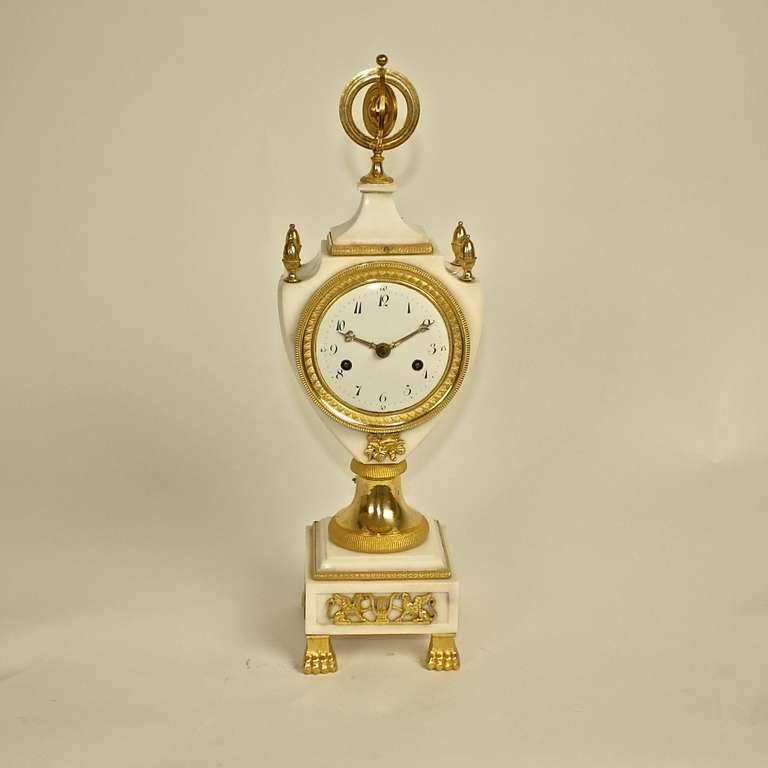 Louis XVI white marble and gilt bronze marble clock, the white enamel dial with Arabic numerals within a lyra-shaped marble case surmounted by pine finials and centred by an armillary dial, raised on a circular stem above a stepped square marble