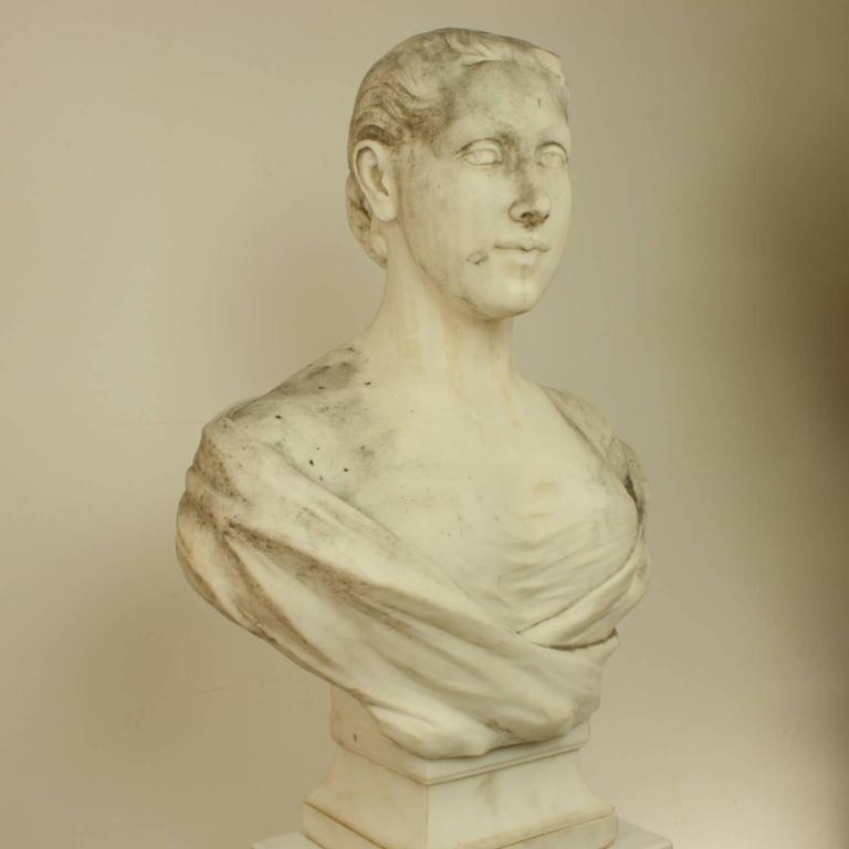 The marble bust facing frontal with her eyes looking to her right. The hair fastened in a skillfull knot behind, the drapery covers her shoulders and breasts, with another section underneath. The young woman displays an observing gaze and knowing