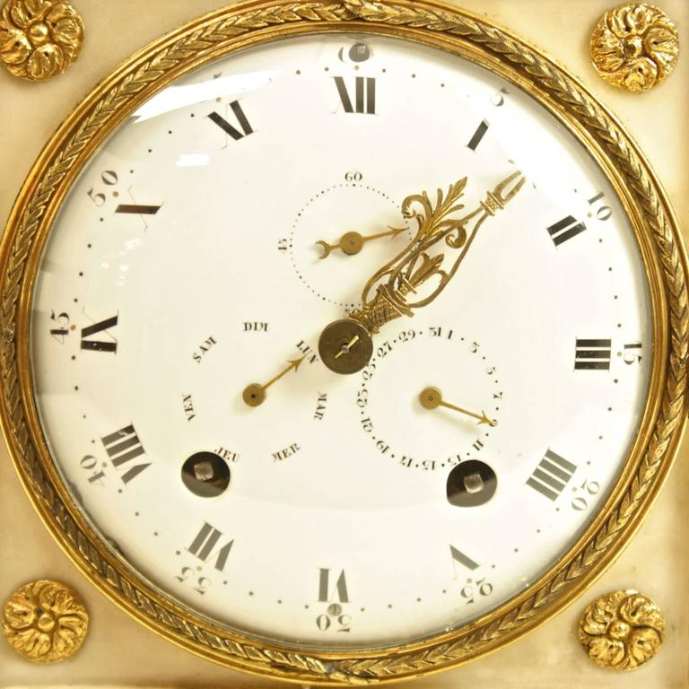 A large late 18th century white marble and gilt-bronze mantel clock, the white enamel dial with Roman numerals inset with three subsidiary dials: One indicating the day of the week, another the day of the month and a second dial. The whole contained