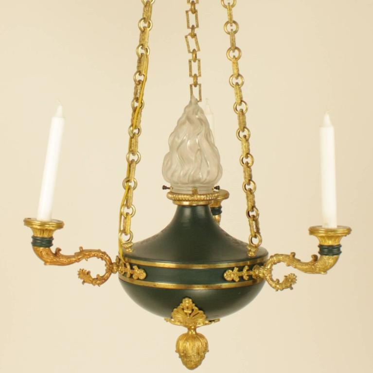 Empire style gilt bronze and green tole three-light candelier, the circular corona decorated with palmettes above the acanthus leave finial, the link chains connecting to the green painted tole font, supporting three foliate scrolled candle branches