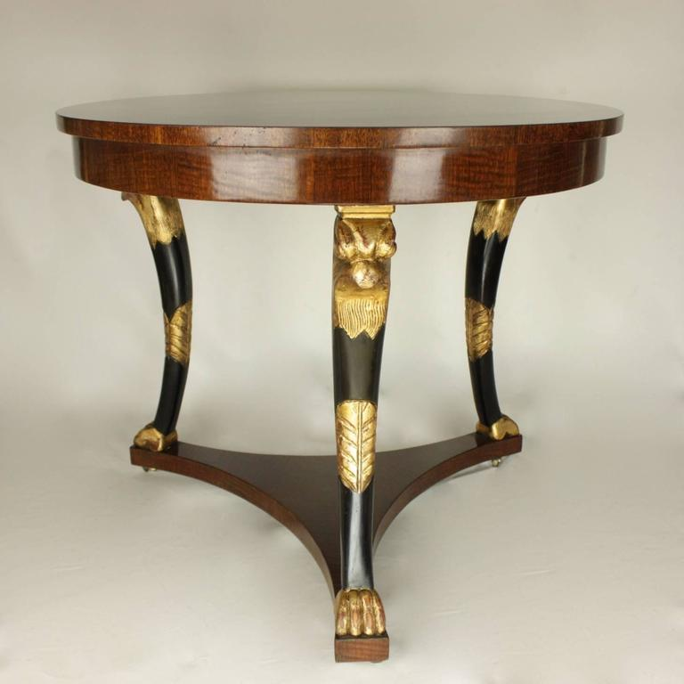 Late 19th century Empire style centre table with an eye-catching mahogany veneered tabletop and horus headed giltwood and ebonized legs. Horus is one of the most significant ancient Egyptian deities - he was the divine representation of the living