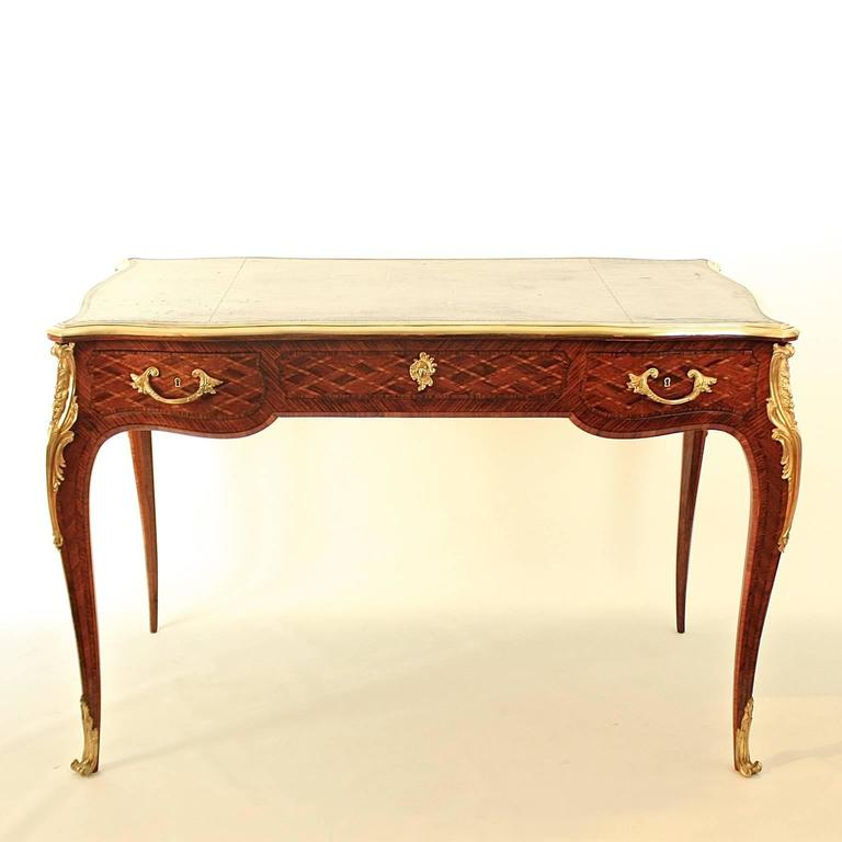 A 19th century Louis XV style gilt bronze mounted marquetry bureau plat, with a brass banded tooled serpentine brown leather top with molded edge above three frieze drawers, each finely inlaid with trellis parquetry, the back decorated conformingly