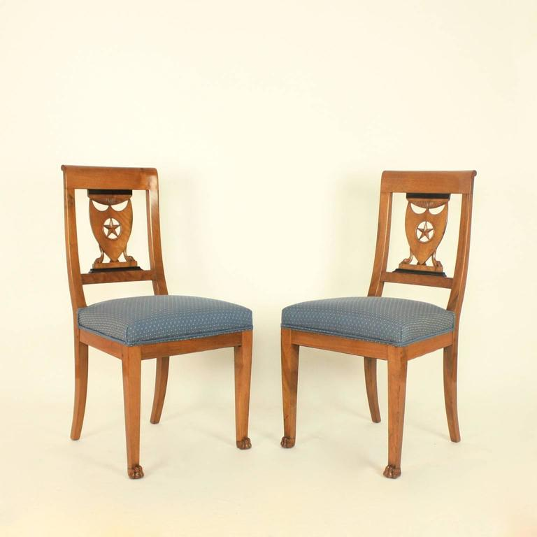 A set of six late 18th century Directoire beechwood side chairs from the workshop of Pierre Marie Balny (died 1832) in the manner of Henri Jacob (1753-1824.)  With wide curved crest rails above a flat pierced lattice backs featuring a shield (a