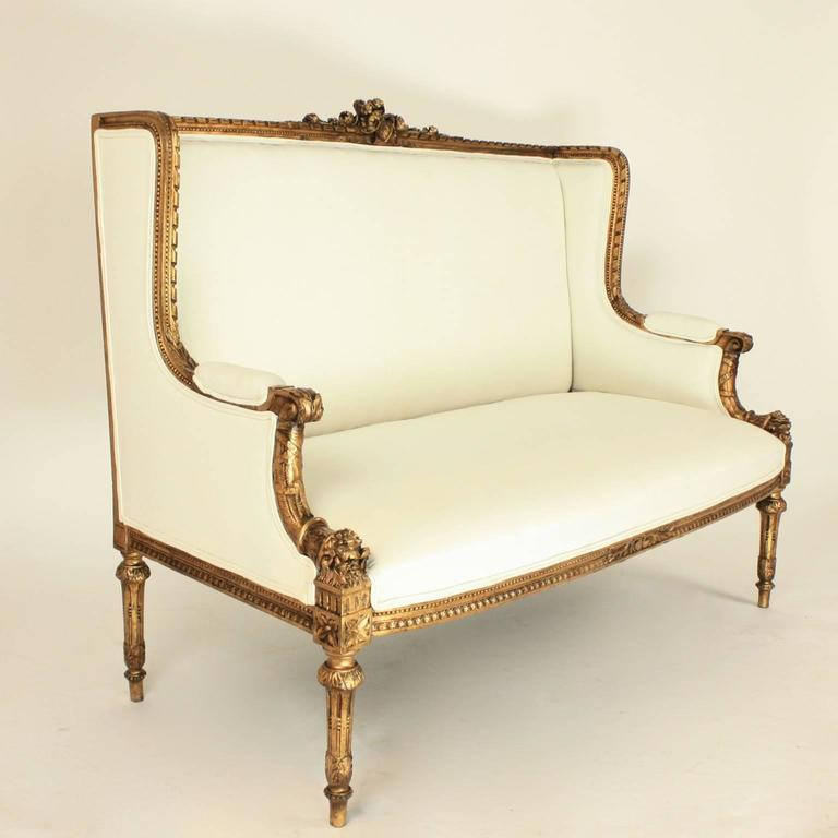A fine 19th century Louis XVI style wingback giltwood settee covered with a fine vintage white linen fabric, with a padded rectangular back and arms and with a carved cresting of a basket and ribbon tied roses spilling out of it. The top rail with a