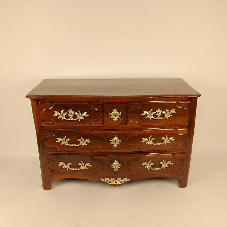 Early 18th century Regence walnut commode with gilt-bronze mounts. The commode has a fashionable curved profile to the front. With a beautifully polished walnut top above three top drawers and two full length drawers below, with rounded corners and