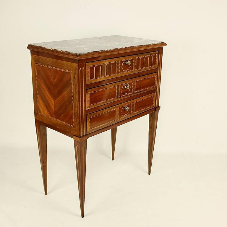 Late 18th century Louis XVI side table or ' Table Chiffoniere' in the manner of Nicolas Petit (1732-1791), with a rectangular inset dark red marble top above three drawers, decorated with fillet marquetry, the sides and square tapering legs inlaid