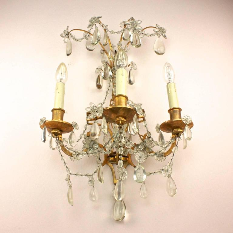 A pair of Regency style Maison Bagues three branch wall sconce or wall lights, each with splays of flowerheads on top, its back plate issuing three S-shaped candle arms hang with drops and beautifully arranged crystal flowers.