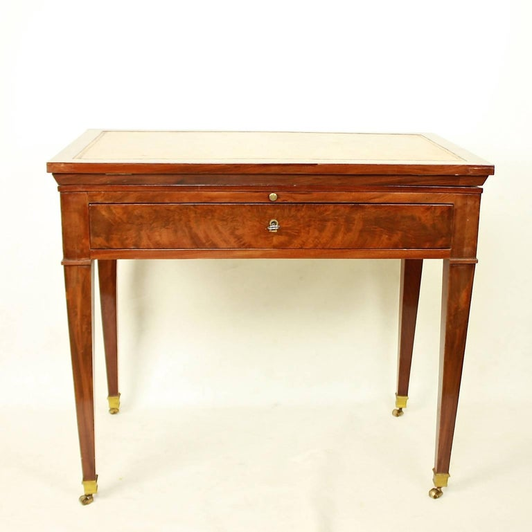 A late 18th century Directoire mahogany architect's table. A mechanical table with a double-hinged ratcheted top and the original gold-tooled brown leather lined writing surface, veneered in beautifully, if rather pale, flame-grained polished