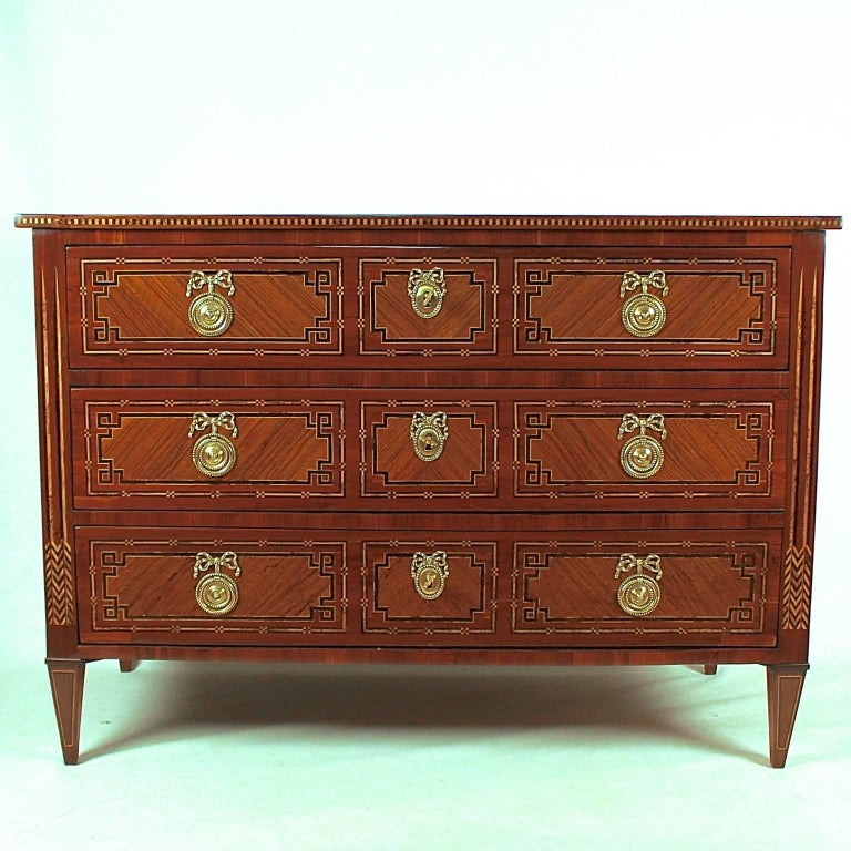 Important South-West German neoclassical chest of drawers of high craftsmanship. The three-drawer pinewood carcass veneered in walnut, plum, maple and other woods. The drawers with three mirror-veneered panels, with checkered inlaid banding and