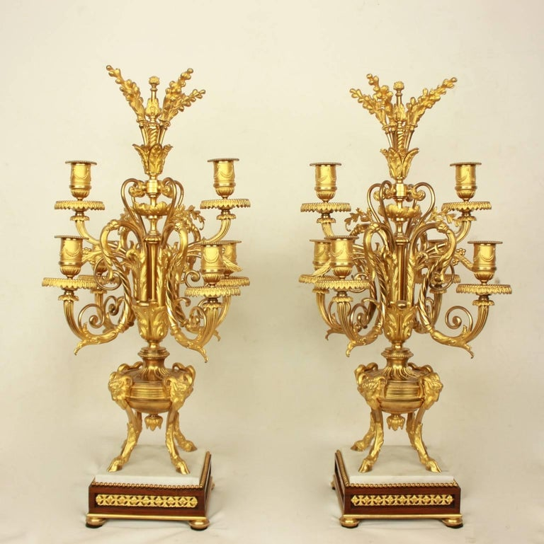 Pair of Louis XVI style ormolu candelabras, each with six scrolling candle arms and corresponding sockets and drip plates raised from a foliate cast central baluster. The central shaft emanating from a fluted urn supported by four rams on a square