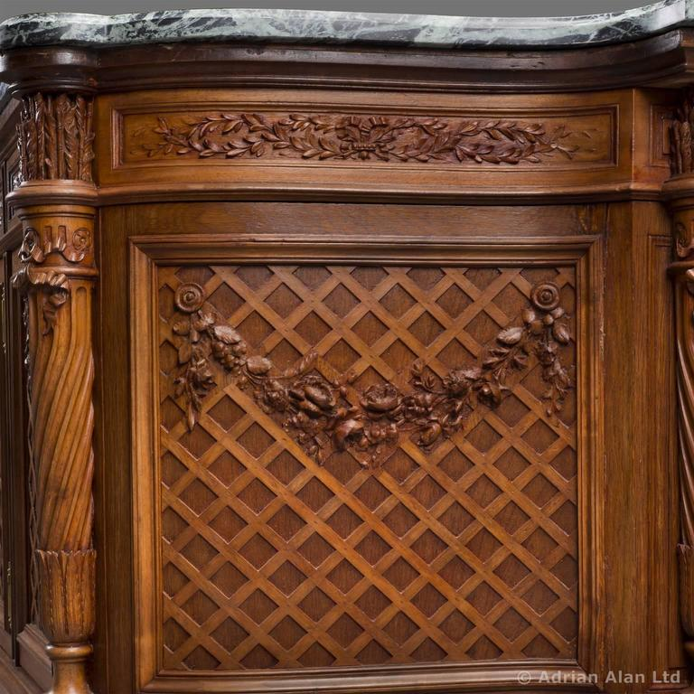 A fine Louis XVI style carved beech side cabinet with a Vert de Mer marble top by Maison Grimard.