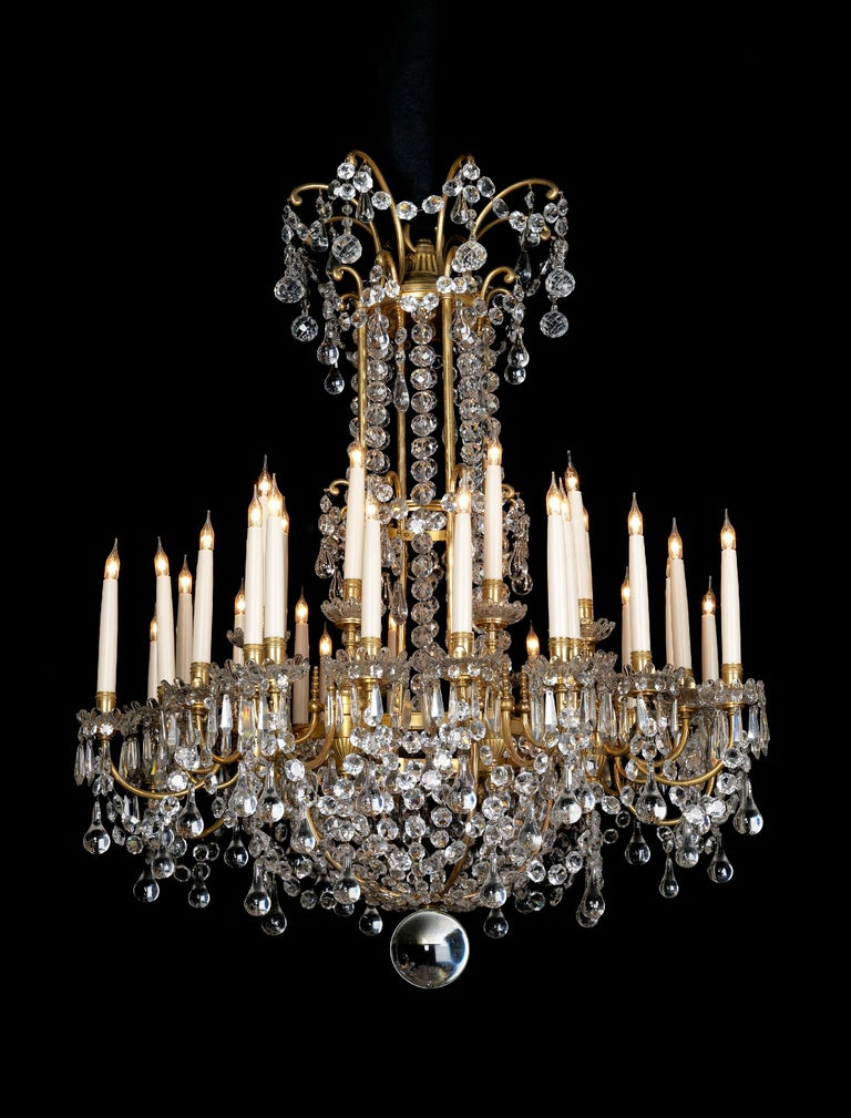 A Louis XVI Style Gilt-Bronze and Cut-Glass Thirty-Two-Light Chandelier by La Compagnie des Cristalleries de Baccarat.   Paris, circa 1890.  This fine chandelier has a gilt-bronze frame with a tiered stem and circular band issuing scrolling