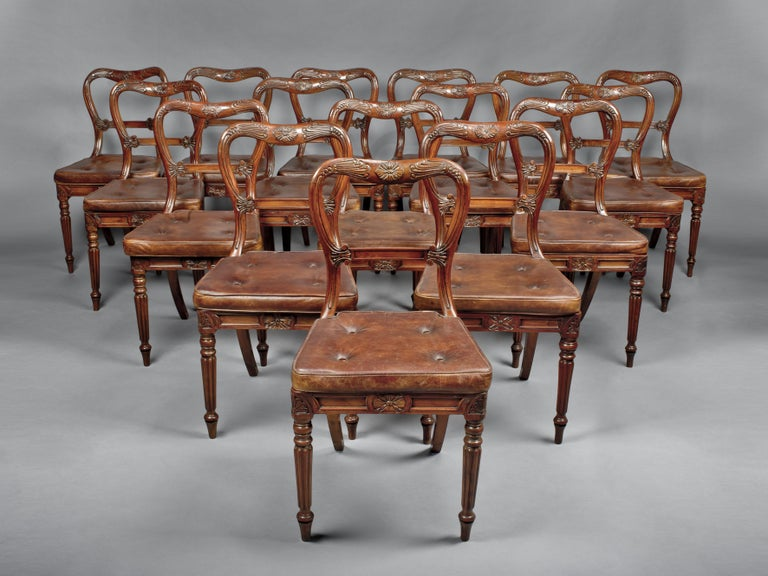 A set of 18 red walnut dining chairs attributed to Gillows.  English, circa 1830.  A set of 18 red walnut fining chairs attributed to Gillows. Each chair has a waisted balloon back, with incised foliage and panelled horizontal splat, above a