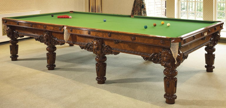 An exceptional carved walnut full size billiard table and accessories by Cox & Yeman.  London, circa 1880.   One end bearing an ivorine label 'Cox & Yeman / Billiard Table Manufacturers / 184 BROMPTON ROAD, / London'.   The Billiard table
