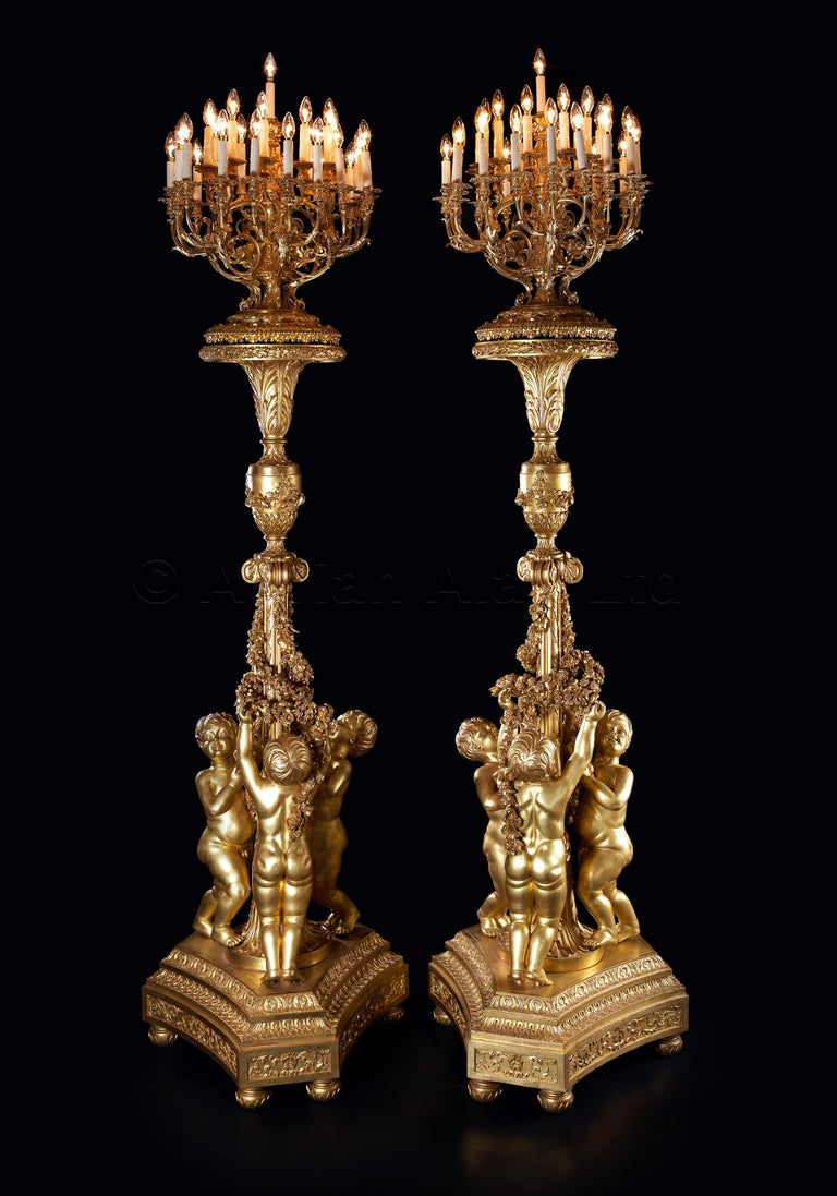 An important pair of monumental thirty-one-light giltwood torchères after the model by Jacques Gondoin for the Hall of Mirrors At the Palace of Versailles.