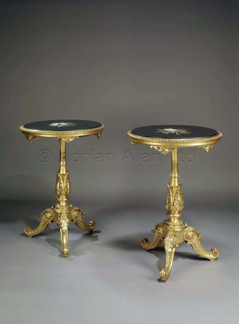 A pair of Rococo style giltwood gueridons, with pietre dure marble tops.  Italian, circa 1880.   The technique of pietre dure is typical of Florence, where it was developed at the end of the 16th century and is still in use today. Referred to as